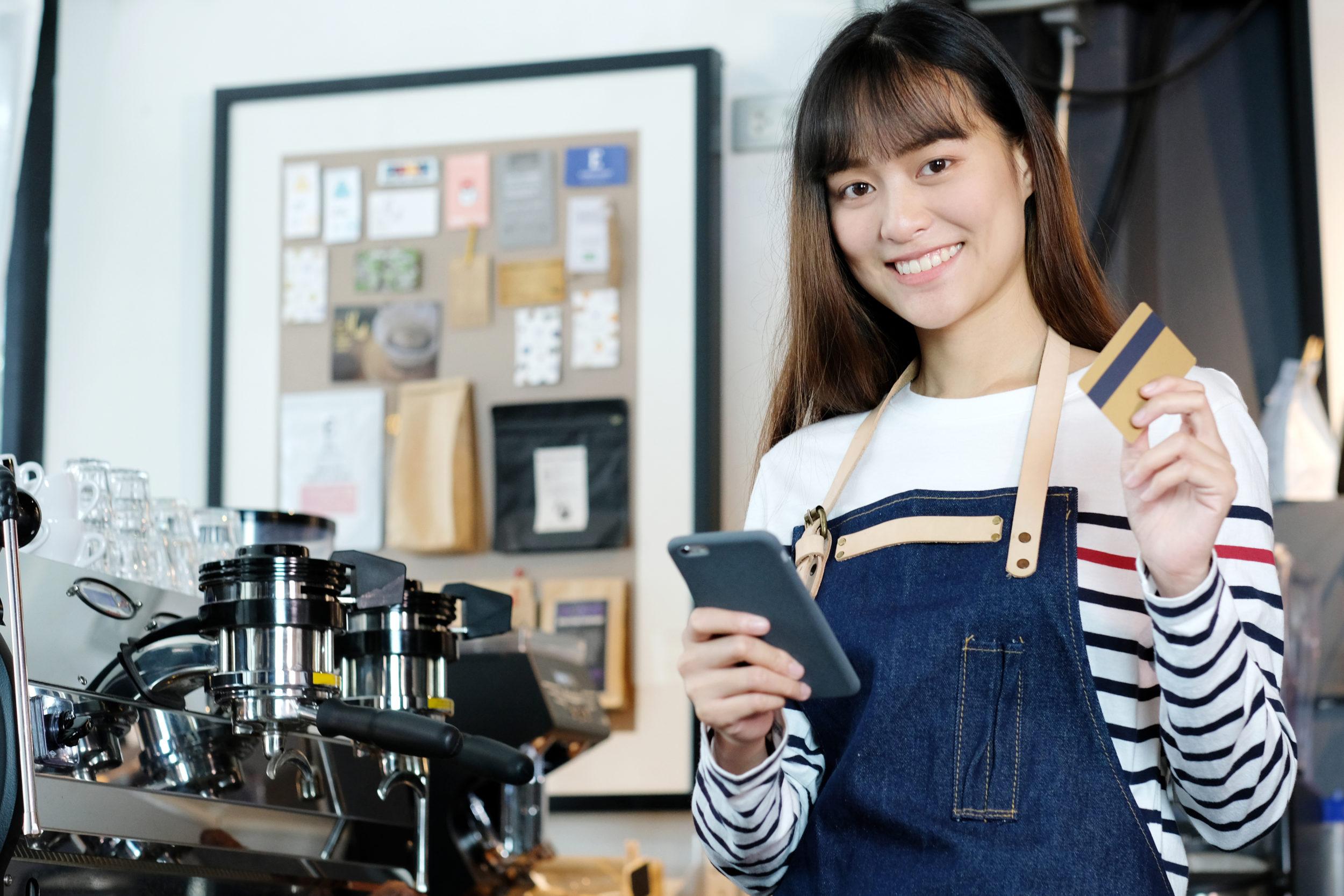 Jeune femme tenant un smartphone et une carte de crédit