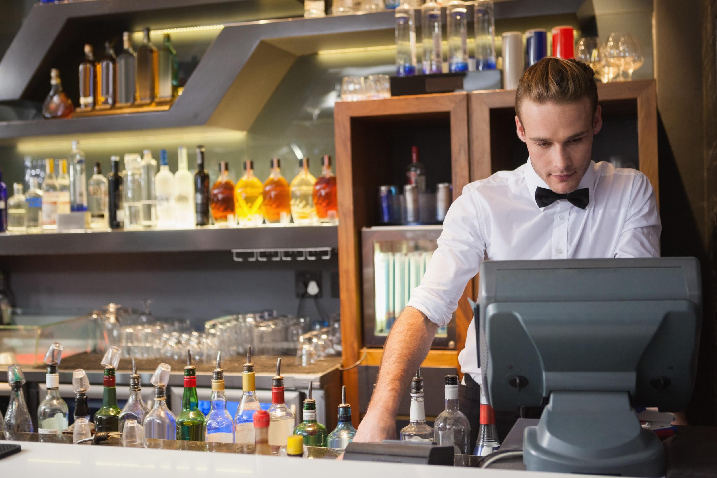 Jeune barman derrière une caisse enregistreuse dans un bar