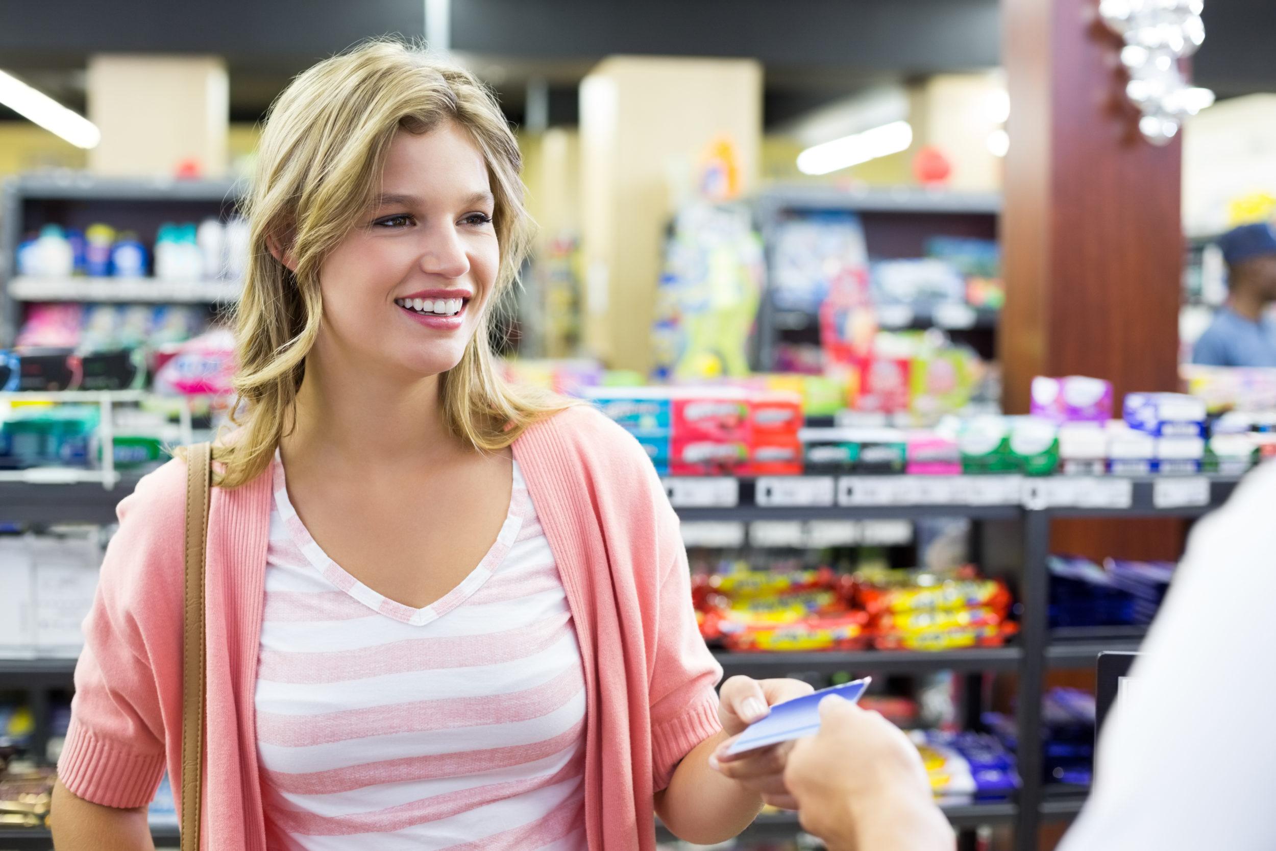 Femme effectuant un achat dans un commerce à l'aide d'une carte de crédit