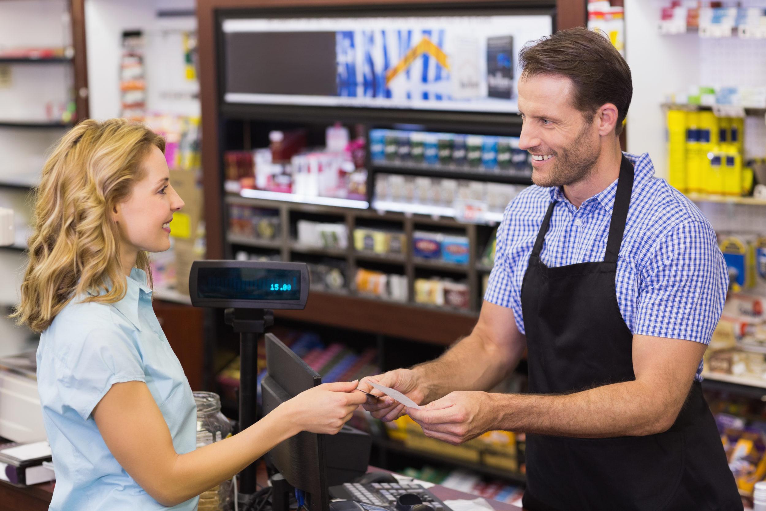 Femme effectuant un achat avec une carte de crédit dans un commerce