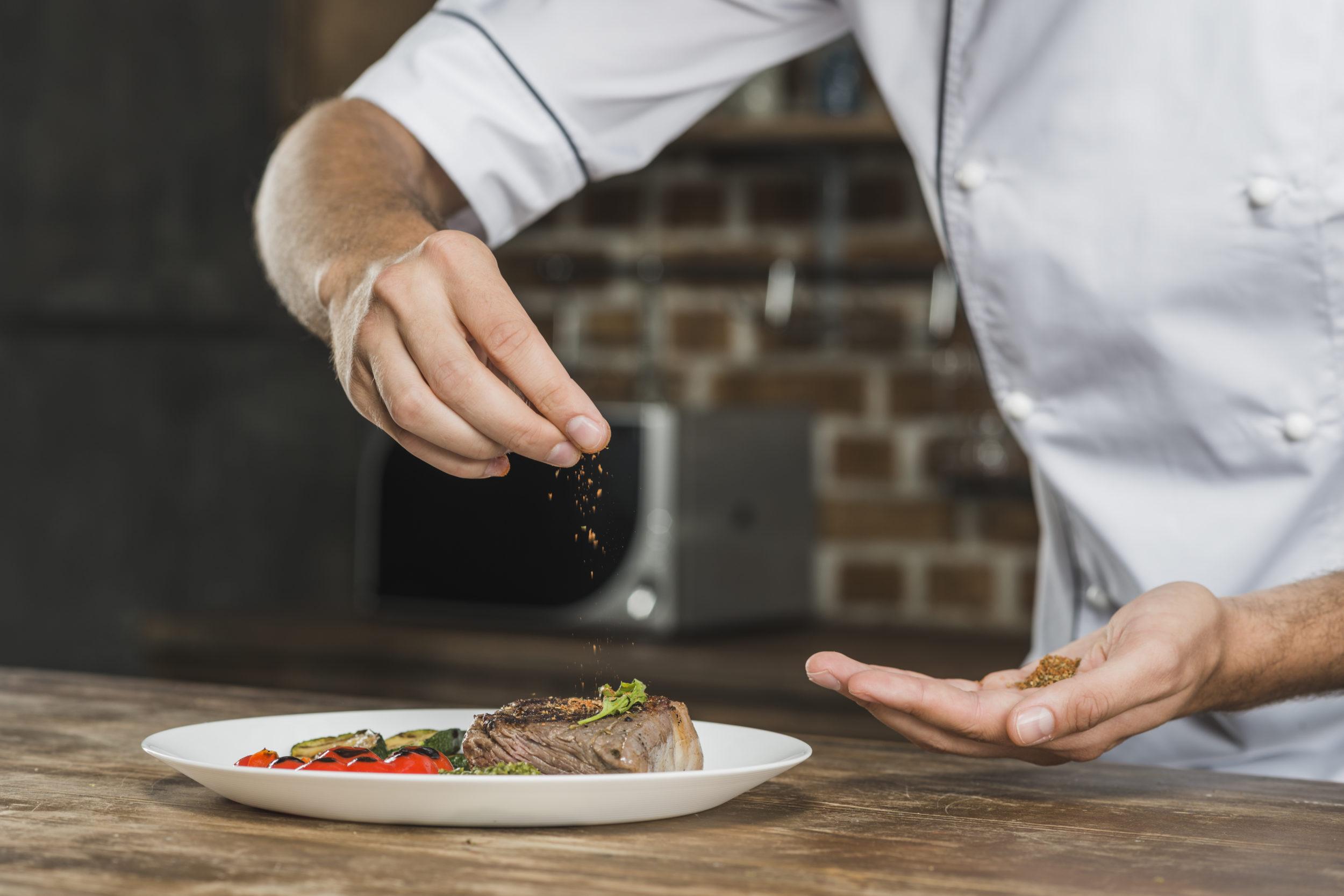 Cuisinier assaisonnant un plat